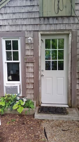 As you approach the front door of our Tiny House you can see the AC in the living room window and to the right would be the small porch and left a little bistro set