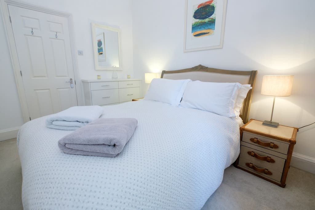 Comfortable king size bed with fresh white linen