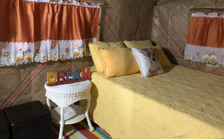 Comfy queen-sized cushioned wood bed, wicker side table, bamboo pillow, silk curtains, native leaf mats