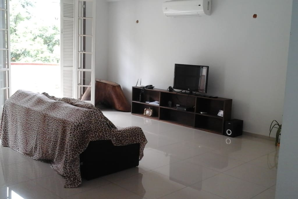 Living room with cable TV & Wi-Fi. Doors leasd to balcony.