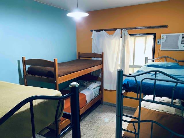 Habitación con 6 camas y aire acondicionado.