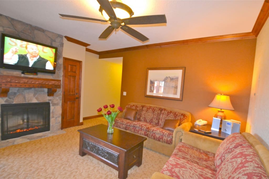 Living room / family room with comfortable furnishings, gas fireplace, flatscreen TV, pull out queen size sofa bed and private balcony.