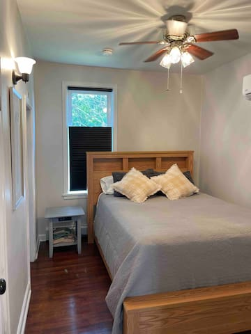 Bedroom is well lit, has a brand new mattress and box spring, room darkening shades, a ceiling fan, and wall air unit.