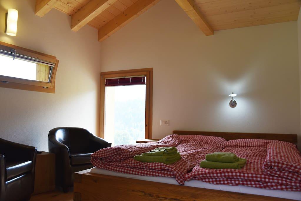 Das lichtdurchflutete Zimmer bietet Platz für ein grosses Bett, einen Schrank und eine kleine Sitzecke mit Fernseher und Ausblick zum gemütlichen Beisammensitzen.