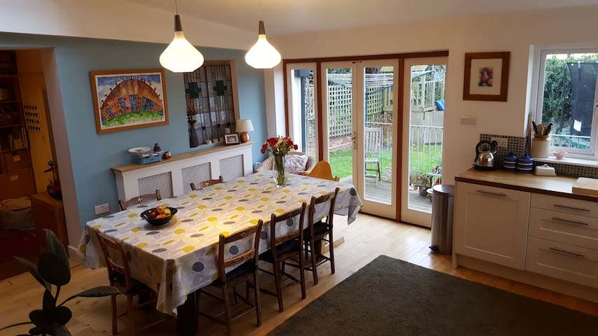 Large dining table seating at least 8 in a very sociable kitchen-dining room opening onto the 'snug', playroom, and overlooking the decking area and enclosed rear garden: takes the stress out of catering while looking after the kids.