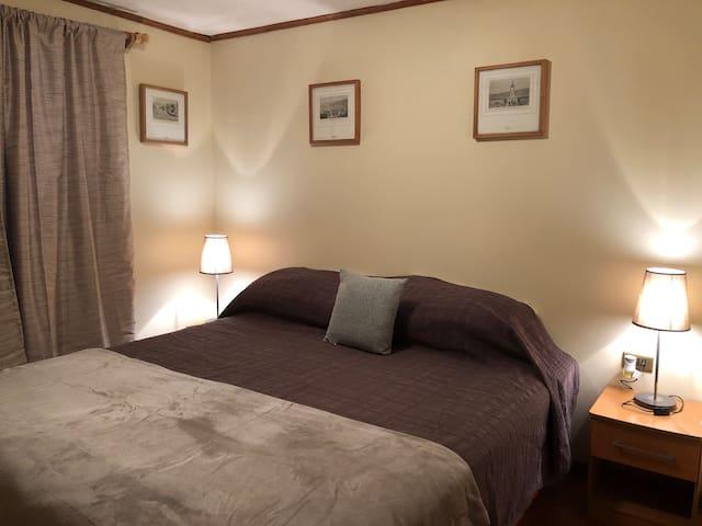 Dormitorio cama Queen con ventanal hacia terraza.