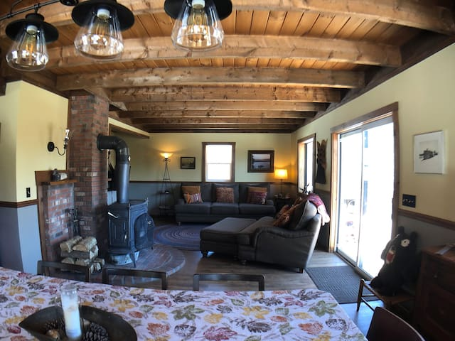 Cozy living room with large couch and loveseat next to the woodstove. Access to large balcony with gorgeous views.