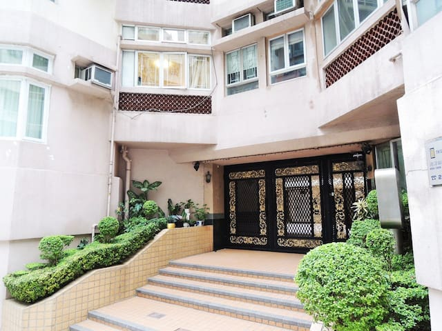 Apartment complex entrance. The complex has 24-hour security guards and the neighbourhood is one of the safest and most laid-back for travellers staying on Hong Kong island, harbourside.