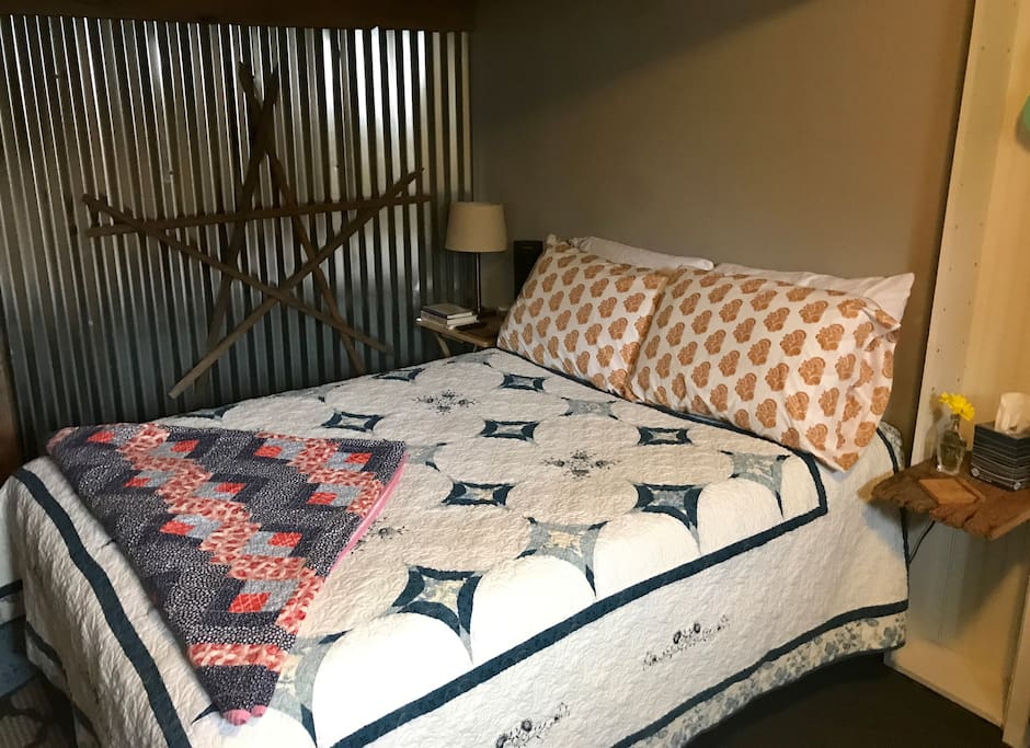 Full-size bed with foam topper and four pillows. Tobacco stake star wall hanging.
