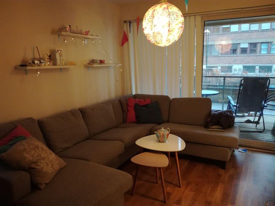 Stue med stor sofa og store glassvindu ut mot koselig balkong