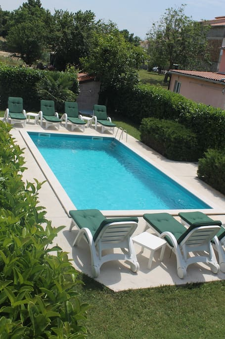 The swimming pool behind the apartman , common with another two apartams.