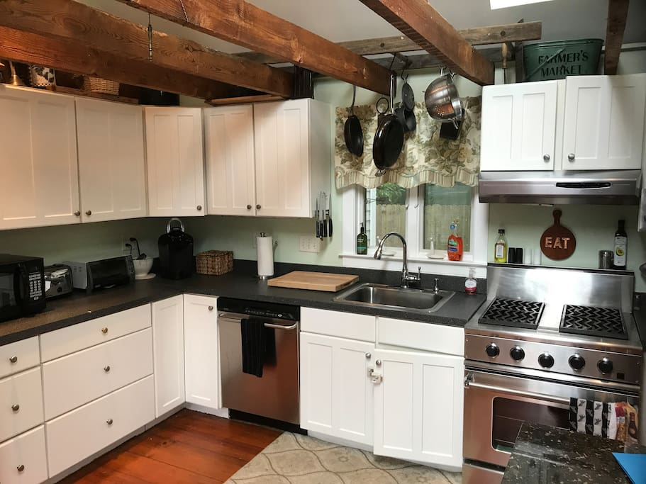 Well equipped kitchen with commercial DCS range and exposed beams.