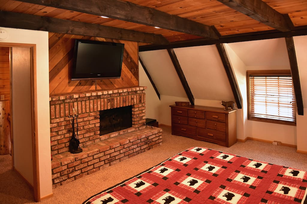 Master bedroom with fireplace, flatscreen TV and a King bed.