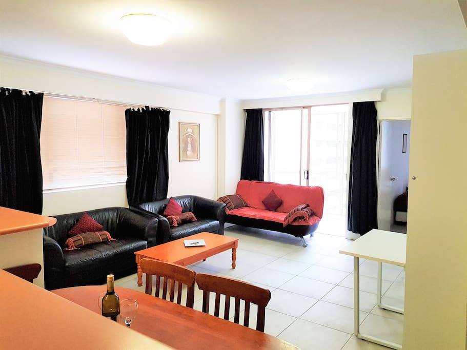Large living room with dining suite, lounge suite, TV, sofa bed, wall beds with desk, and balcony.