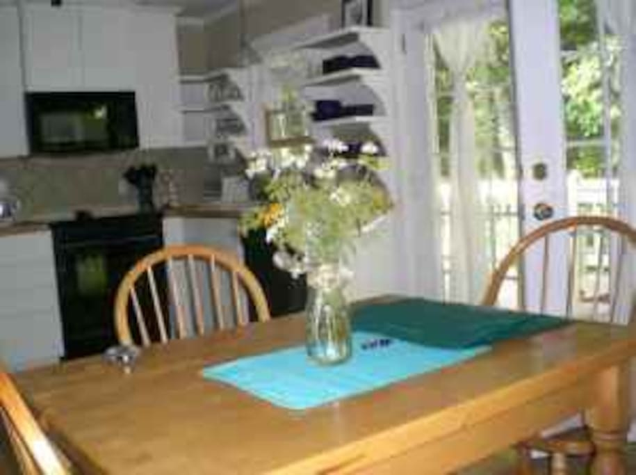 Kitchen/dining room with a view of the french doors that is your private entrance and deck.  Kitchen has stainless steel full size refrigerator, microwave, full electric stove/oven, dishwasher.