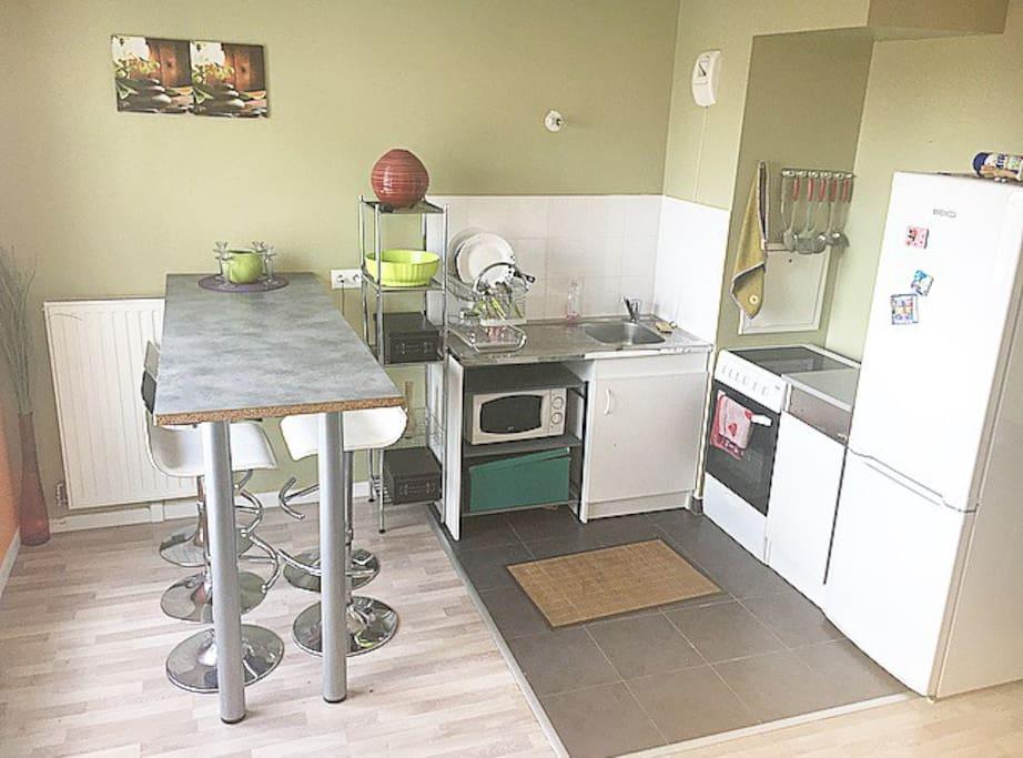 Kitchenette avec bar intégré, vaisselle disponible, micro-onde également, four et 3 plaques. Vue sur la ville lors de vos repas