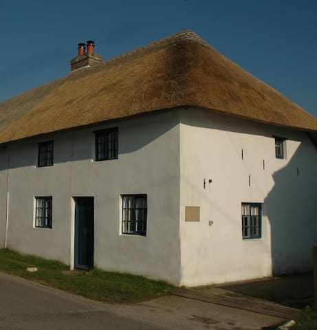 Thatched cottage with large garden in village