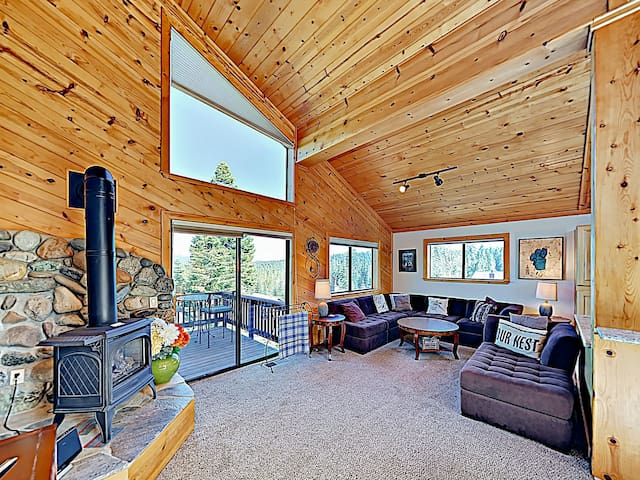Vaulted ceilings and large windows flood the living area with natural light. (Please note that the fireplace/stove is not operational.)