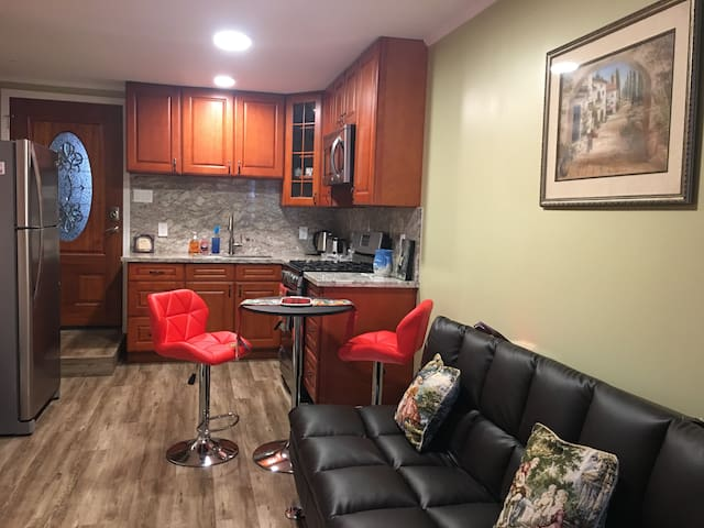 View from the seating area into the full equipped kitchen with Frigidaire stainless appliances (fridge, oven and microwave). Also you will find a toaster, electric tea kettle and coffee maker.