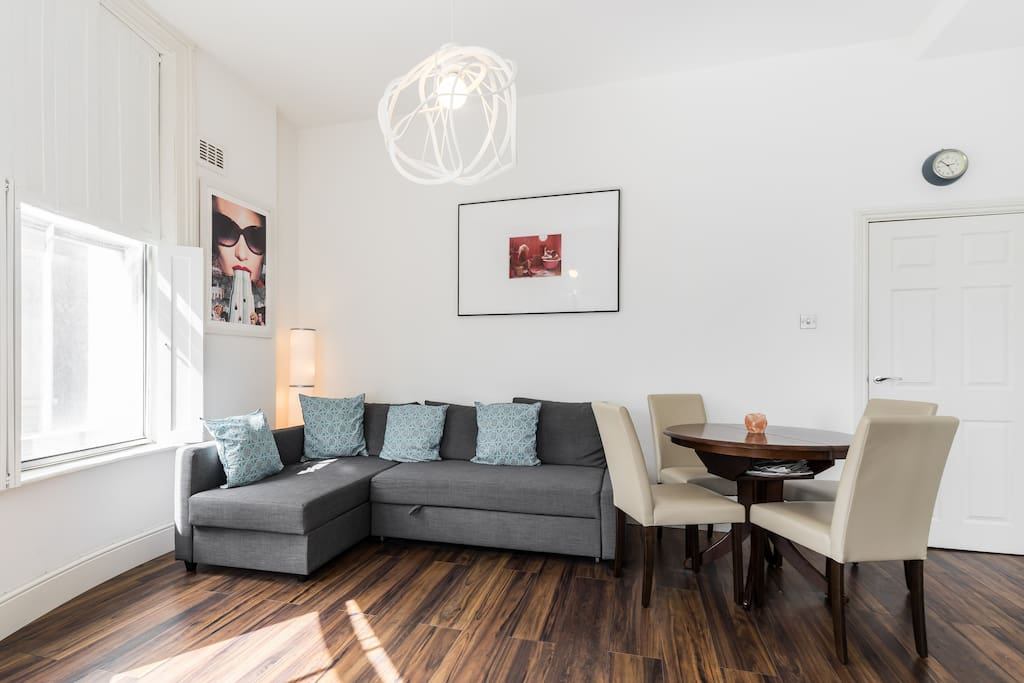 There is a lovely high ceilinged living room with comfy double sofa bed