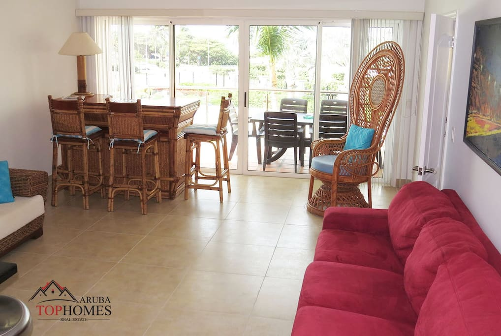 Living Room area leading to one of the balconies with pool and beach view.