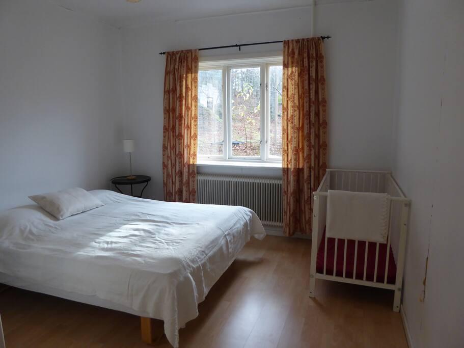 Sovrummet på bottenvåningen med dubbelsäng och en spjälsäng.