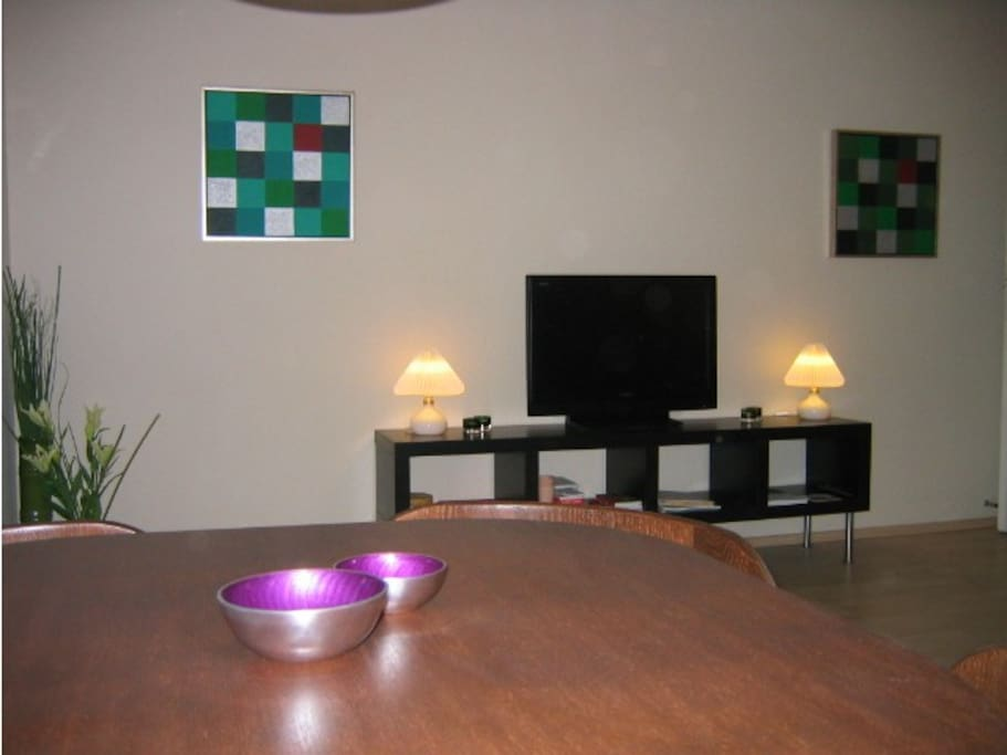 Living room viewed over dining table towards TV-bench.