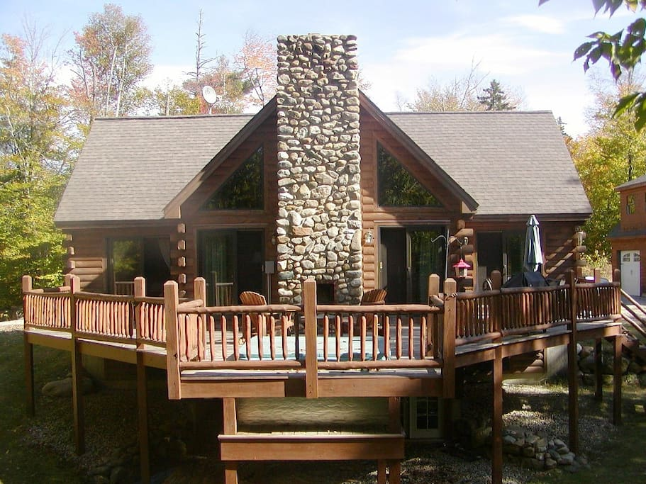 View of the back deck with sunken hot tub and outdoor fireplace.