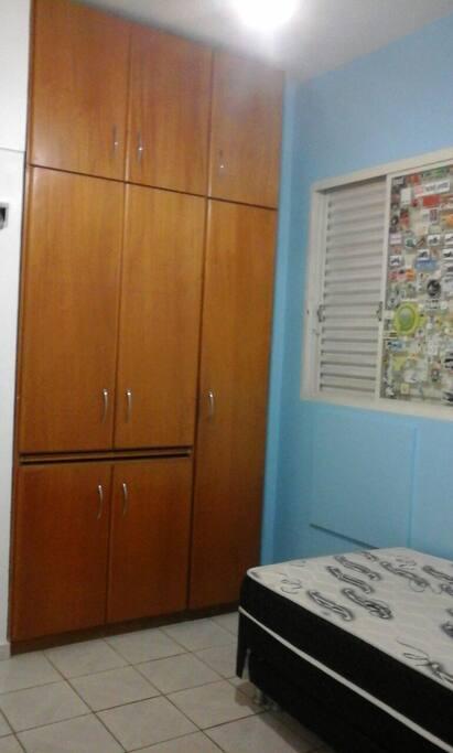 Quarto com tv, cama box com cama auxiliar, ventilador de teto, ar condicionado e armário embutido.