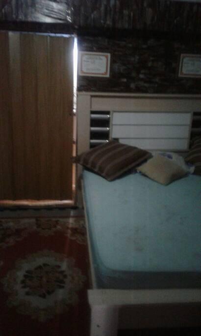 este é quarto tem uma cama de casal .um armário e uma cama de solteiro