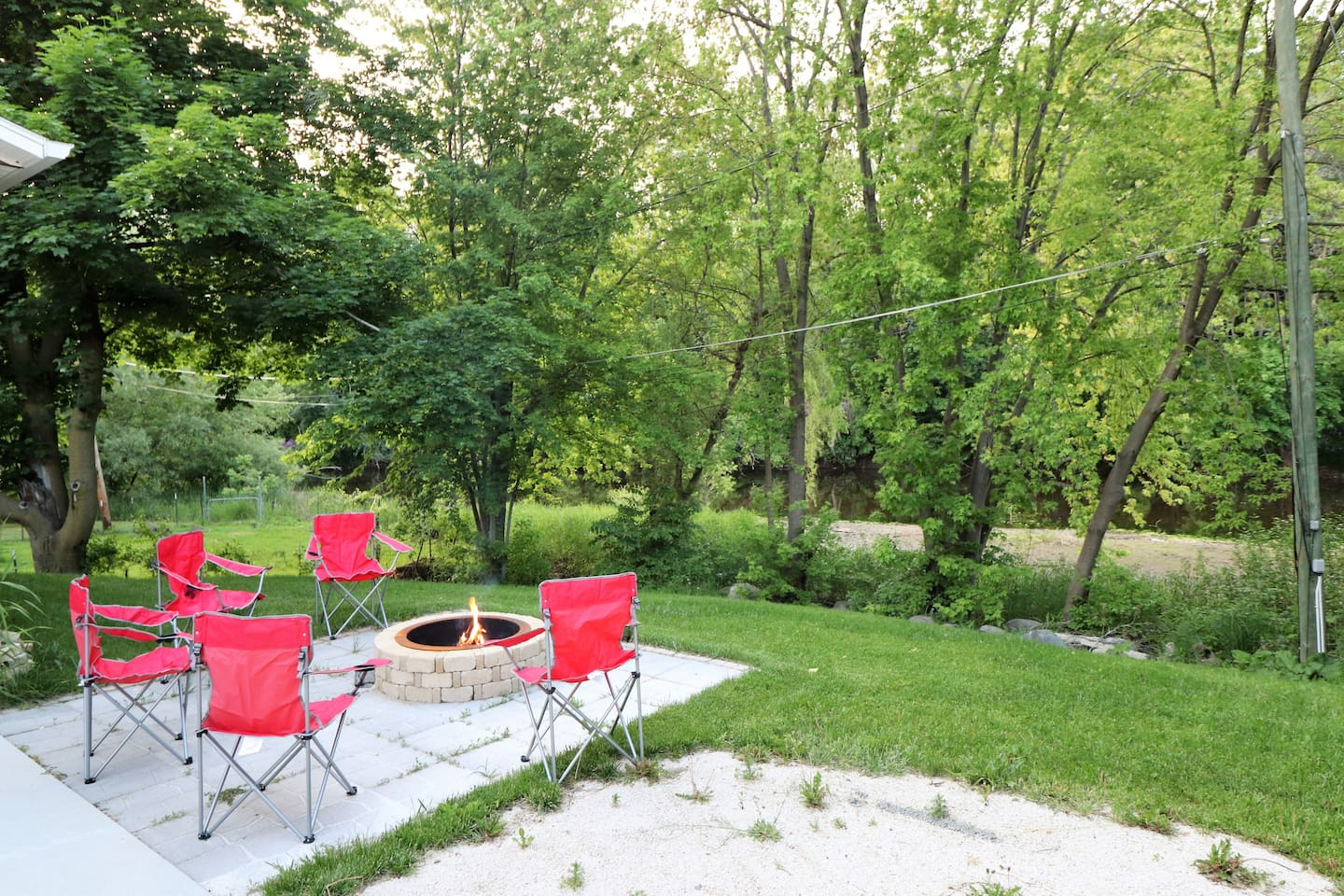 Fire pit and backyard backing up to the Sheboygan River. Enjoy your evening with friends around a fire.