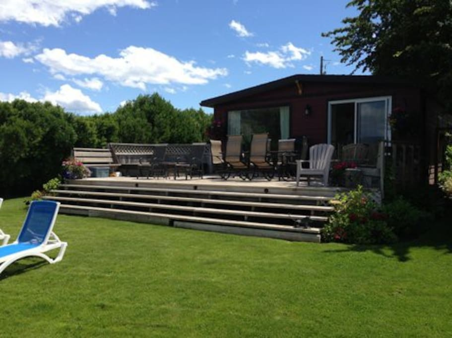 Spacious deck with jaw dropping views, bbq, dining table and large hot tub
