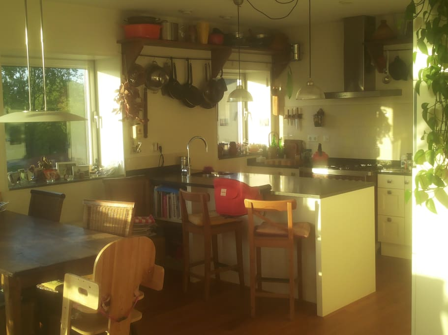 This is our kitchen with a kitchen island and bar, our favorite spot for drinking a good glass of wine.
