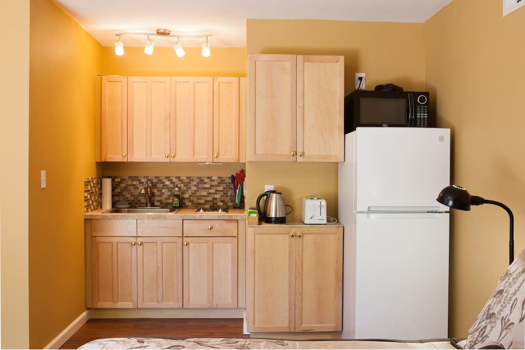 Kitchenette, electric hot plate, microwave, and cabinets stocked with plates, cups, silverware, cooking utensils, pots and pans.