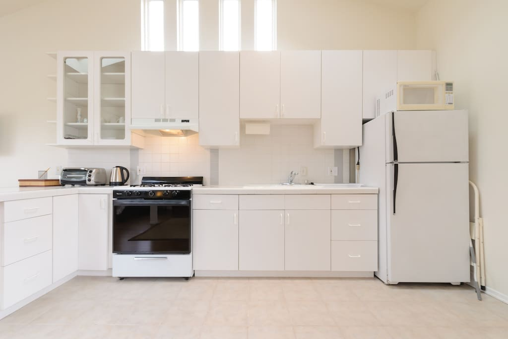 Fully stocked kitchen with stove, toaster oven, elec kettle, utensils