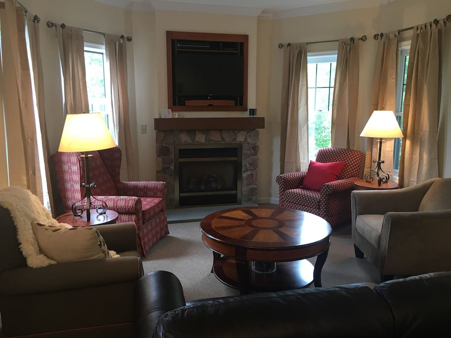 Living area with couch, four chairs, gas fireplace and Direct TV cable. Sanctuary views during the fall and winter. When trees are in bloom, open the windows to hear the sounds of the sanctuary out back.