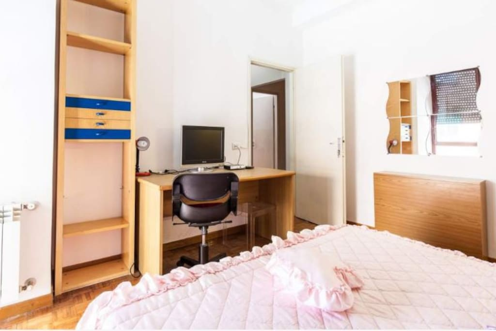 Double bed, desk, tv and bookcase