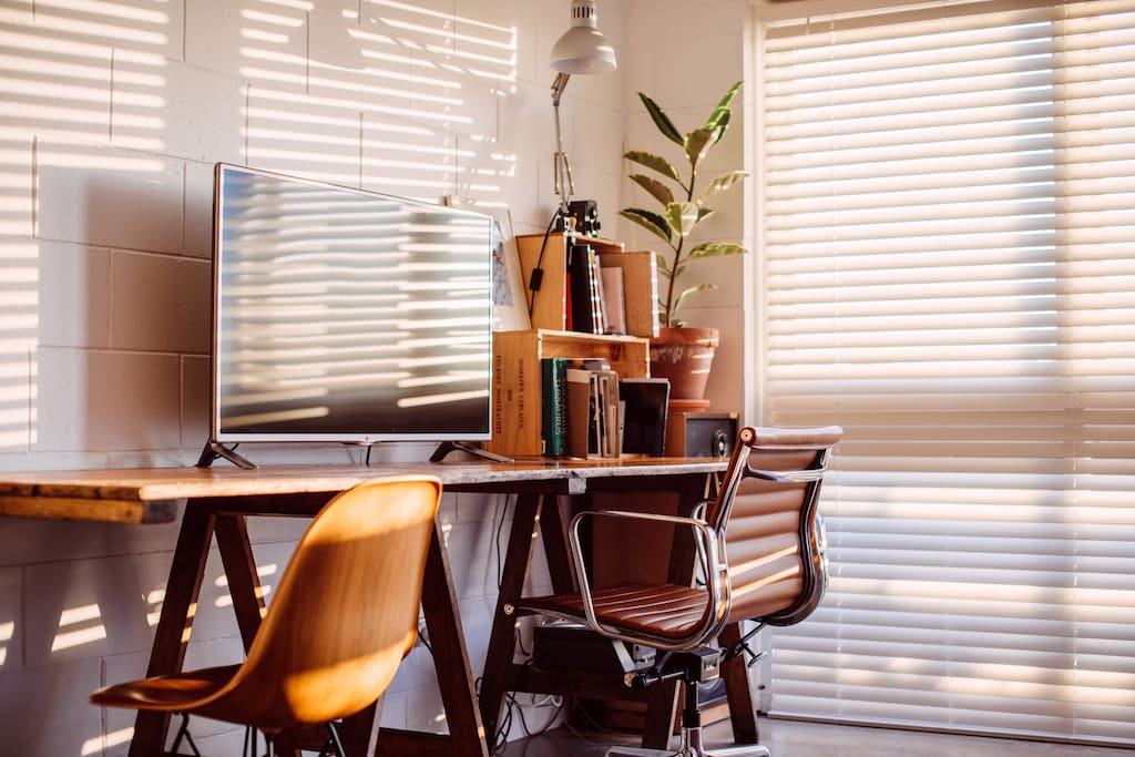 Warm evening light in the living area comes pouring in through the large western-facing windows when the venetian blinds are open.