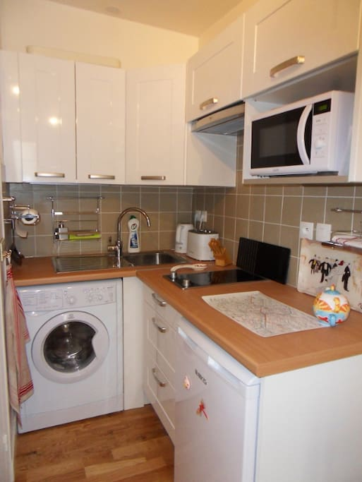 Full equipped kitchen with washing machine/dryer.