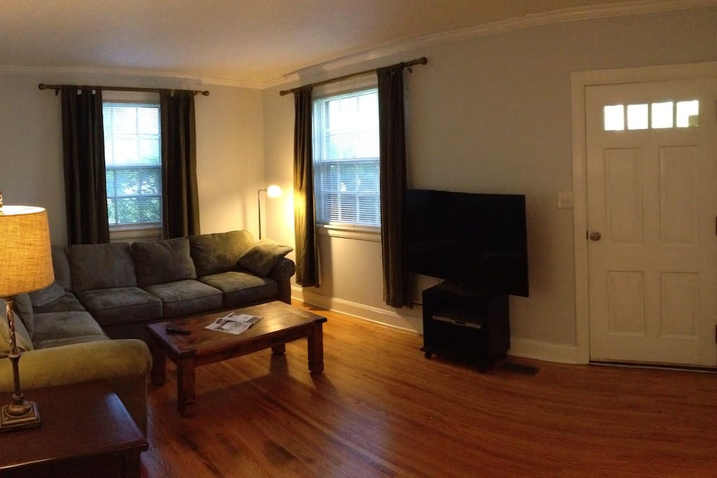 """Living room. Sectional couch with queen size pullout and 55"""" tv."""