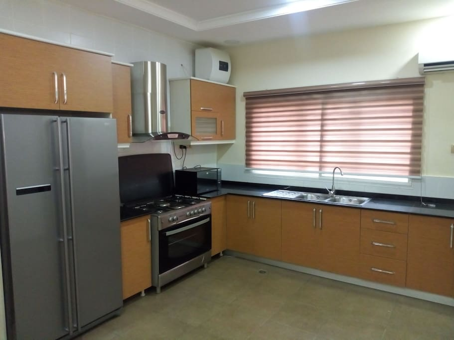 Fitted kitchen with double-door fridge, gascooker, oven, microwave oven, blender, coffee maker etc