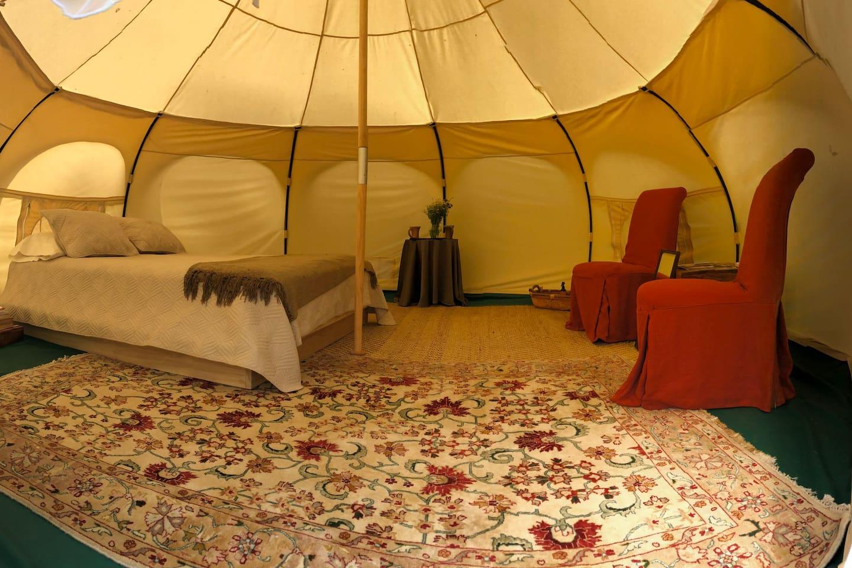 Yurt interior includes queen size bed.