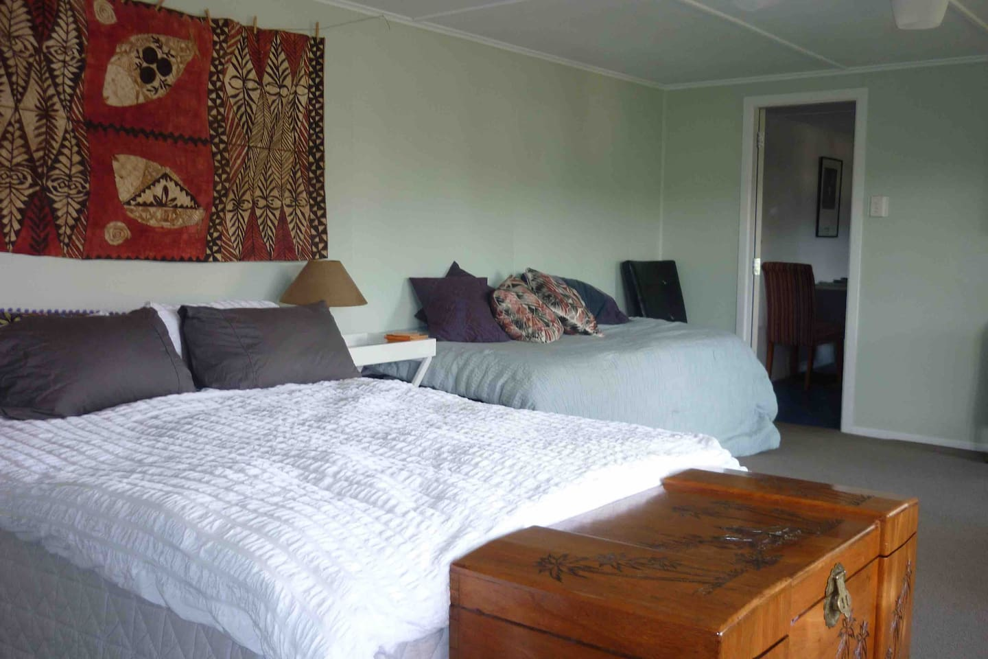 Large room with comfortable queen sized bed, 2 singles beds stacked to create a couch, blanket box.
