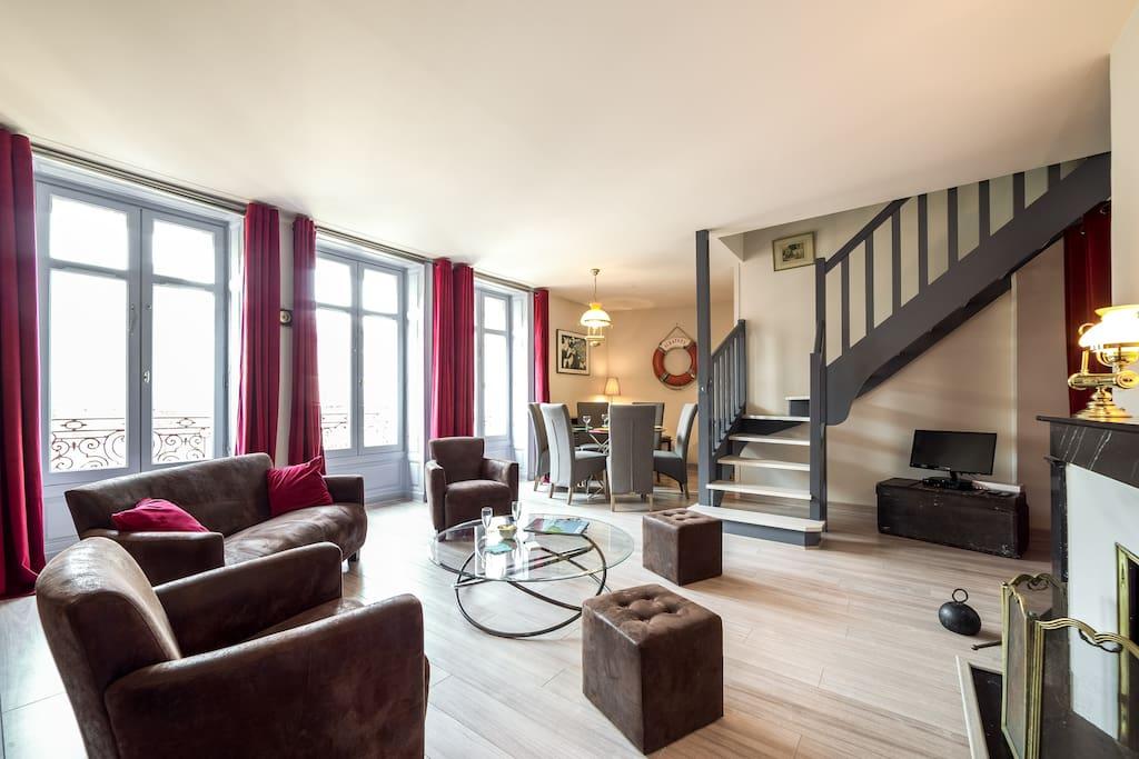 Vue salon et salle à manger avec escalier duplex