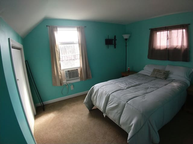 First upstairs bedroom. Full size bed, A/C unit, closet and dresser.