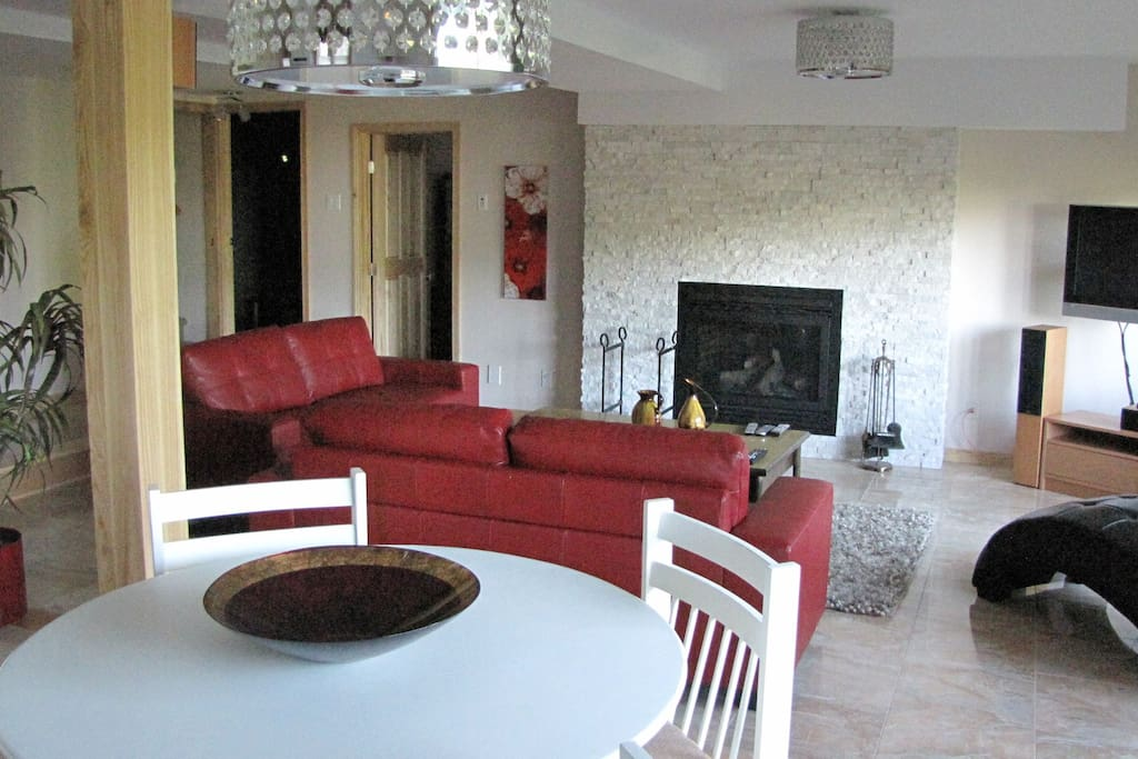 View of Den with red leather sofas and propane gas  2 sided fireplace.