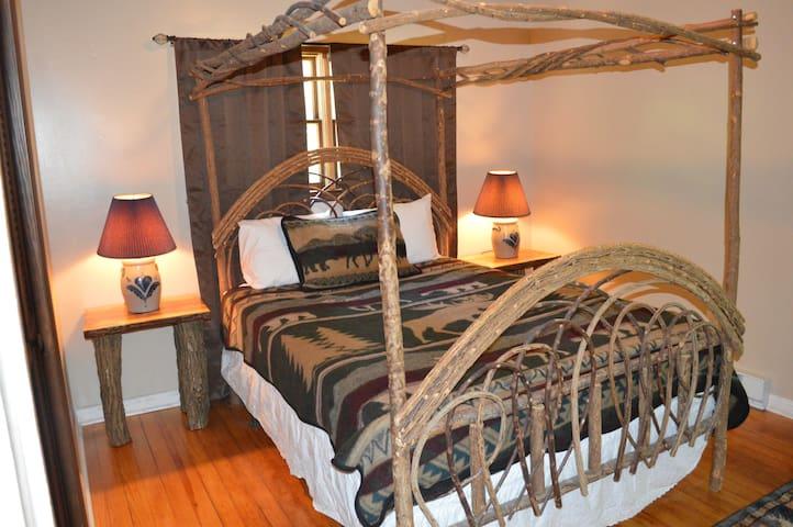 Cozy country bedroom, with bent wood queen bed, night stands, dresser, closet, and sliding door overlooking private porch.