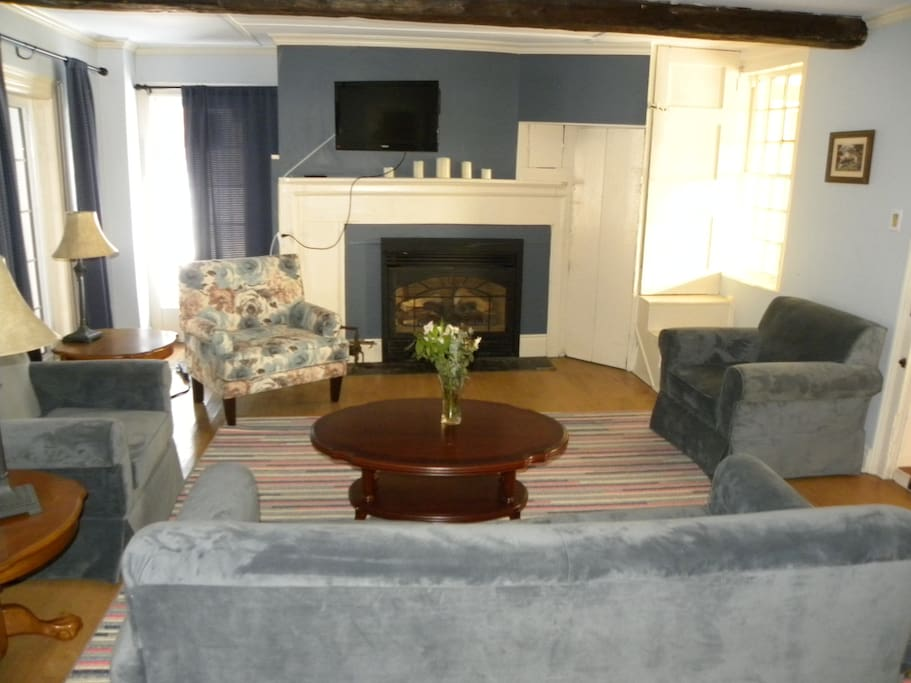 Living Room with gas fireplace 150 year old beams and pullout couch stocked with table games and DVD's