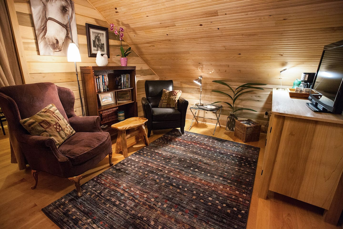 The Library Loft is an apartment inside of The Stables, a barn never used and converted to living and event space. The comfortable living room contains a large selection of books and dvd's for your enjoyment. Large screen TV sits on the wooden hutch.