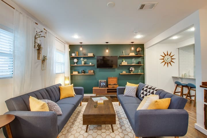 Mid-century inspired open living space: two fold out couches that convert to futon beds, Amazon Fire smart TV with streaming apps, bluetooth speaker, record player, custom dimming Edison lights for good vibes!
